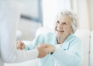 Smiling elderly woman accepts assistance to stand