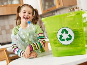 Girl looking at camera and holding plastic bottles for recycling